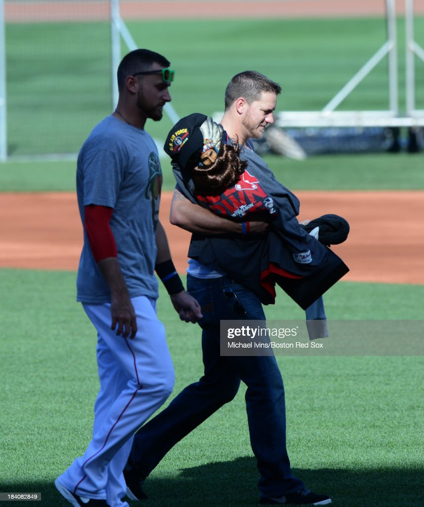 Jake Peavy #44 of the Boston Red Sox walks across the infield with Will Middlebrooks #16 while carrying an indian statue that has become a team totem and normally sits in the clubhouse on October 11, 2013 at Fenway Park in Boston, Masschusetts.