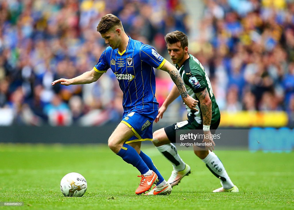 Jake Reeves of Wimbledon under pressure from Graham Carey of Plymouth during the Sky Bet League Two Play Off Final match between Plymouth Argyle and AFC Wimbledon at Wembley Stadium on May 30, 2016 in London, England.