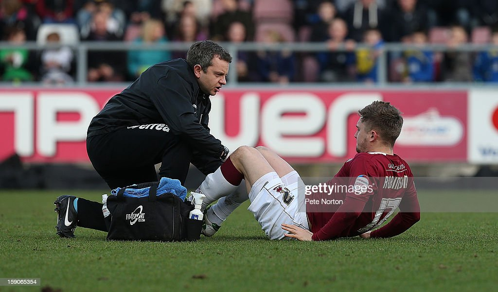Jake Robinson of Northampton Town receives treatment from physio Stuart Barker during the npower League Two match between Northampton Town and Fleetwood Town at Sixfields Stadium on January 5, 2013 in Northampton, England.