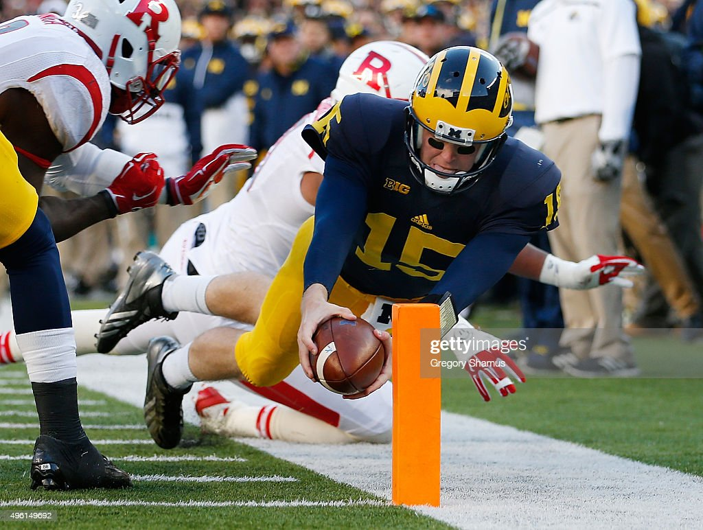 Jake Rudock of the Michigan Wolverines dives for a first quarter touchdown in front of Julian PinnixOdrick of the Rutgers Scarlet Knights on November...