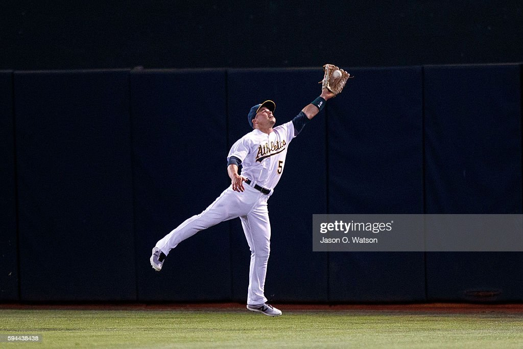 Jake Smolinski of the Oakland Athletics catches a fly ball hit off the bat of Lonnie Chisenhall of the Cleveland Indians during the eighth inning at...