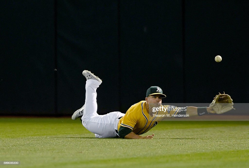 Jake Smolinski #5 of the Oakland Athletics dives for this ball that goes for an RBI triple off the bat of Shawn O'Malley #36 of the Seattle Mariners in the top of the sixth inning at the Oakland Coliseum on August 12, 2016 in Oakland, California.
