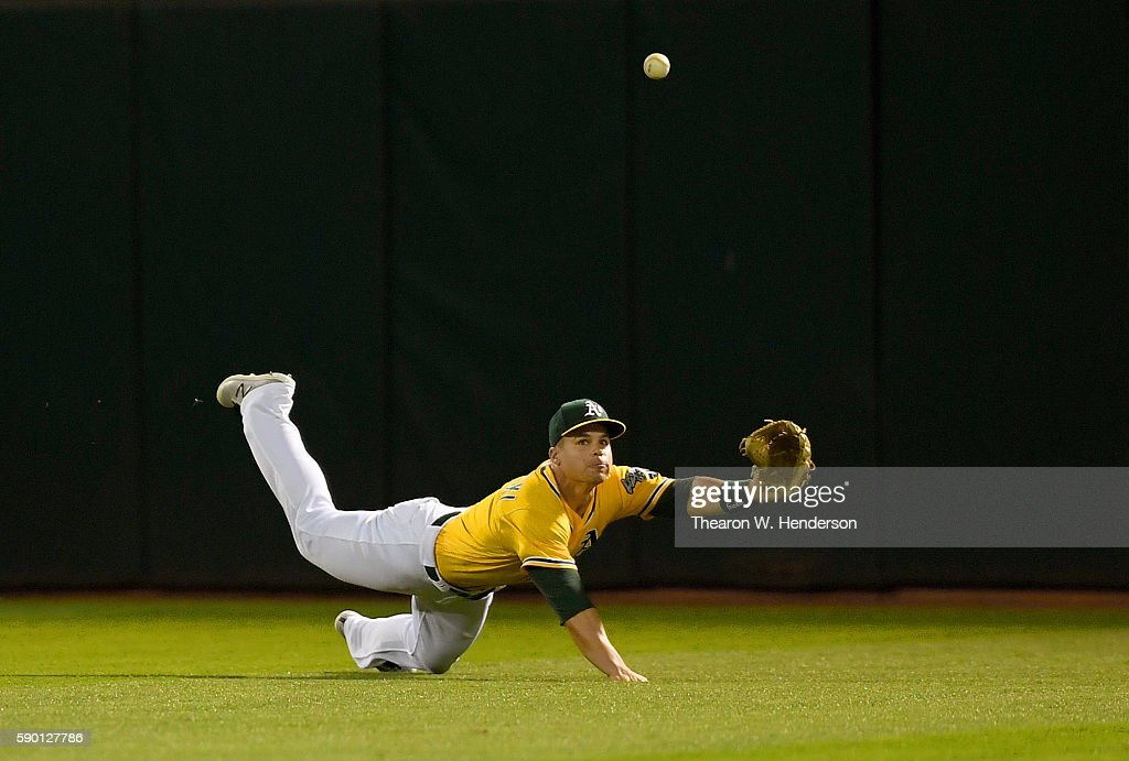 Jake Smolinski #5 of the Oakland Athletics dives for this ball that goes for an rbi triple off the bat of Shawn O'Malley #36 of the Seattle Mariners in the top of the six inning at the Oakland Coliseum on August 12, 2016 in Oakland, California.