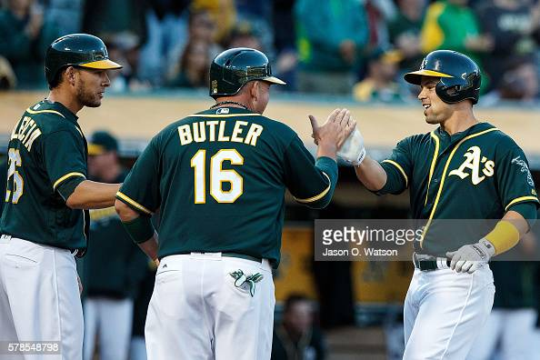 Jake Smolinski of the Oakland Athletics is congratulated by Billy Butler and Danny Valencia after hitting a three run home run against the Tampa Bay...