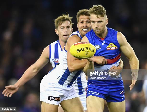 Jake Stringer of the Bulldogs handballs whilst being tackled by Andrew Swallow of the Kangaroos during the round 14 AFL match between the Western...