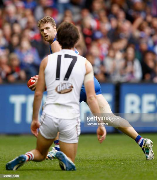 Jake Stringer of the Bulldogs looks back at Dylan Roberton of the Saints after he slipped over during the round 10 AFL match between the Western...