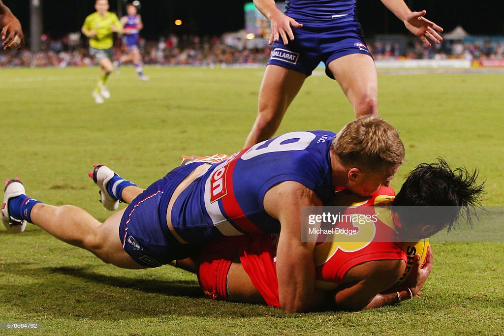 Jake Stringer of the Bulldogs tackles Aaron Hall of the Suns during the round 17 AFL match between the Western Bulldogs and the Gold Coast Suns at...