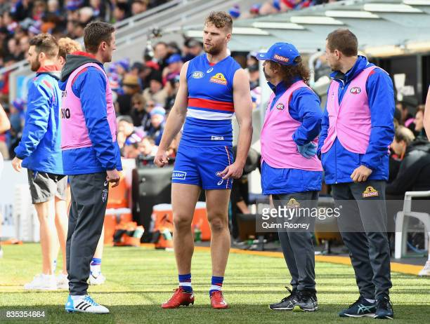 Jake Stringer of the Bulldogs talks to club doctors after hurting his hamstring during the round 22 AFL match between the Western Bulldogs and the...