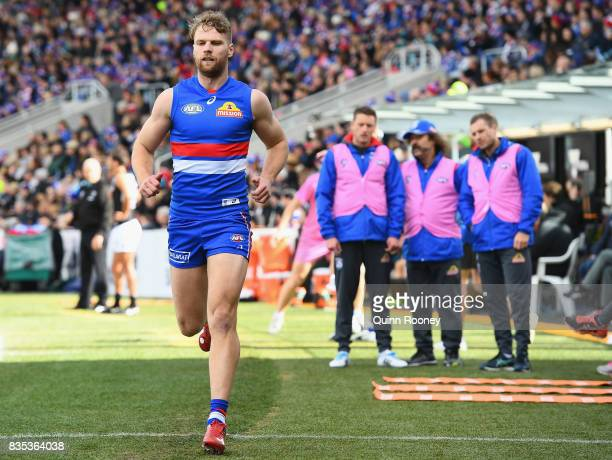 Jake Stringer of the Bulldogs tests his hamstring as club doctors look on during the round 22 AFL match between the Western Bulldogs and the Port...