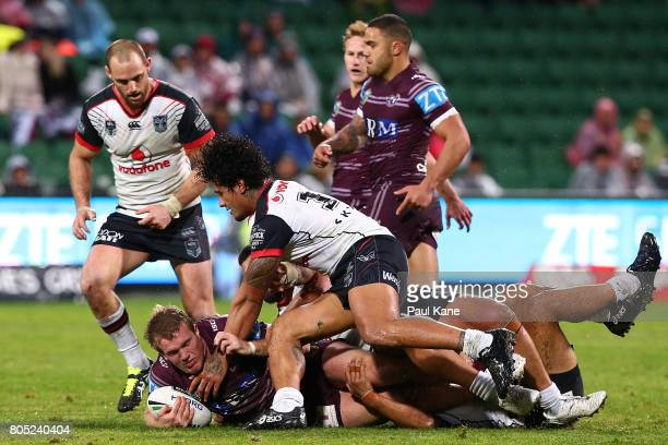 Jake Trbojevic of the Sea Eagles gets tackled by James Gavet and Ben Matulino of the Warriors during the round 17 NRL match between the Manly Sea...