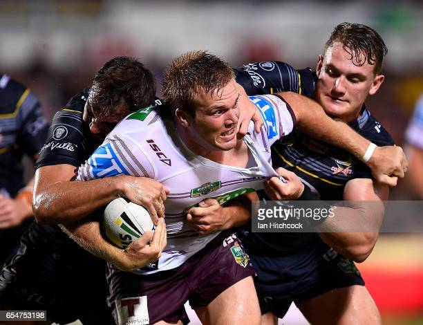 Jake Trbojevic of the Sea Eagles is tackled by Coen Hess and Benjamin Hampton of the Cowboys during the round three NRL match between the North...