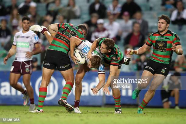 Jake Trbojevic of the Sea Eagles is tackled by Sam Burgess and Cameron Murray of the Rabbitohs during the round nine NRL match between the South...