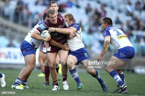 Jake Trbojevic of the Sea Eagles is tackled during the round 24 NRL match between the Canterbury Bulldogs and the Manly Sea Eagles at ANZ Stadium on...