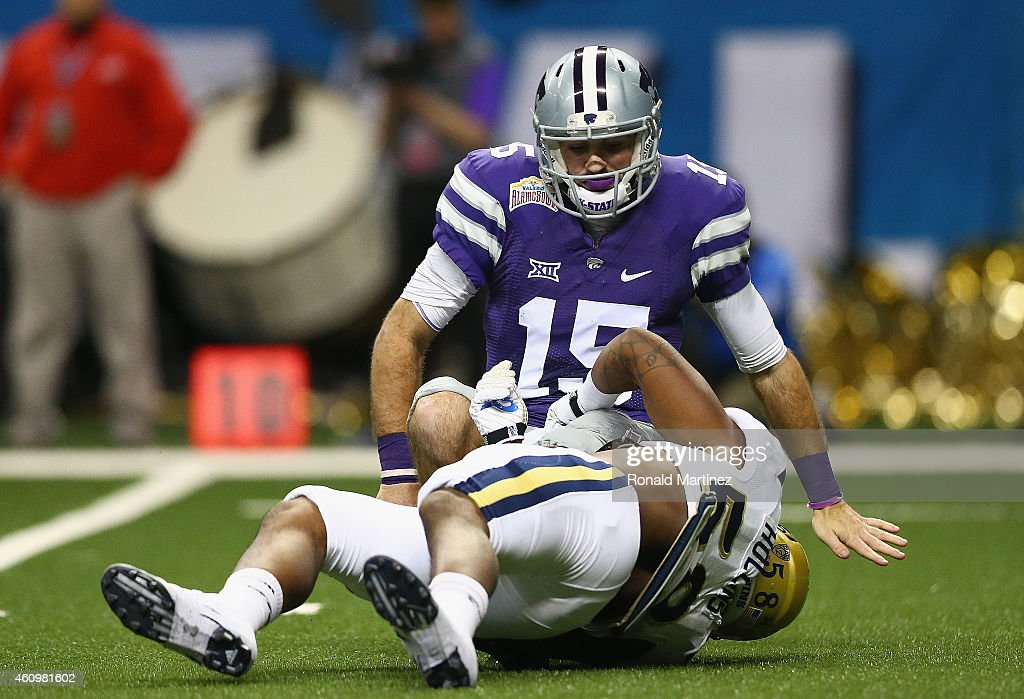 <a gi-track='captionPersonalityLinkClicked' href=/galleries/search?phrase=Jake+Waters&family=editorial&specificpeople=10875996 ng-click='$event.stopPropagation()'>Jake Waters</a> #15 of the Kansas State Wildcats is tackled by Deon Hollins #58 of the UCLA Bruins in the first quarter during the Valero Alamo Bowl at Alamodome on January 2, 2015 in San Antonio, Texas.