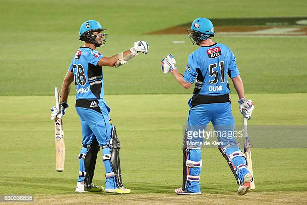 Jake Weatherald congratulates teammate Ben Dunk of the Adelaide Strikers after he reached 50 runs during the Big Bash League match between the...