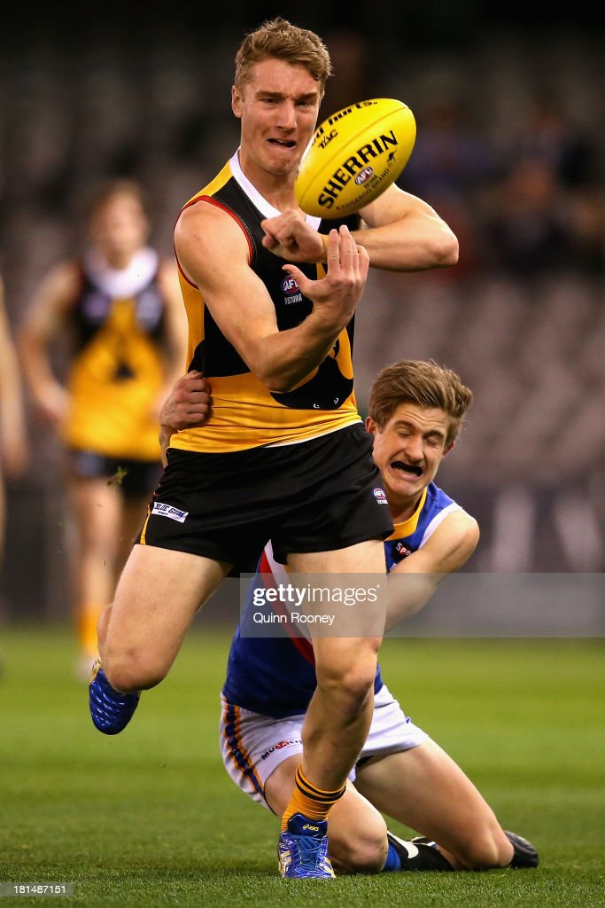 Jake Wilson of the Stingrays handballs whilst being tackled during the TAC Cup final match between Eastern Ranges and the Dandenong Southern Stingrays at Etihad Stadium on September 22, 2013 in Melbourne, Australia.