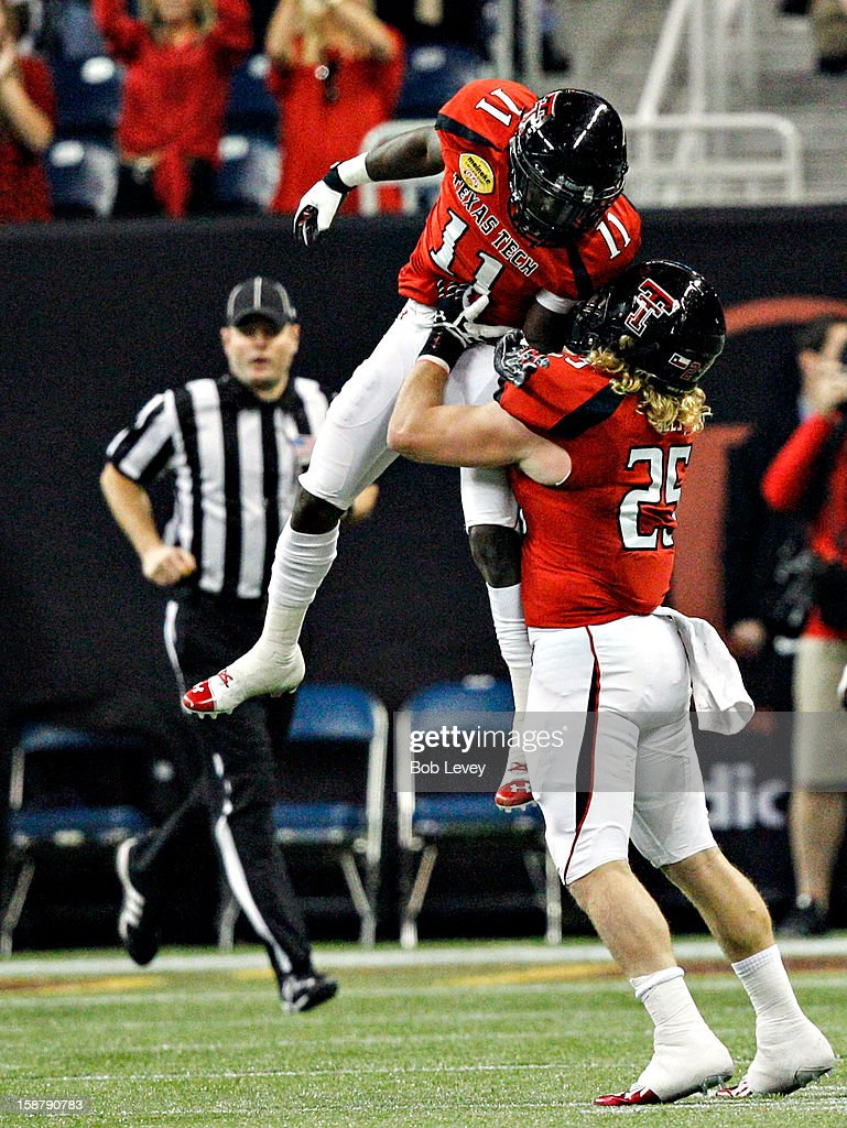 Jakeem Grant #11 of the Texas Tech Red Raiders celebrates with Blake Dees #25 of the Texas Tech Red Raiders after returning a kickoff for 99 yards against the Minnesota Golden Gophers during the Meineke Car Care of Texas Bowl at Reliant Stadium on December 28, 2012 in Houston, Texas. Texas Tech defeated Minnesota 34-31.
