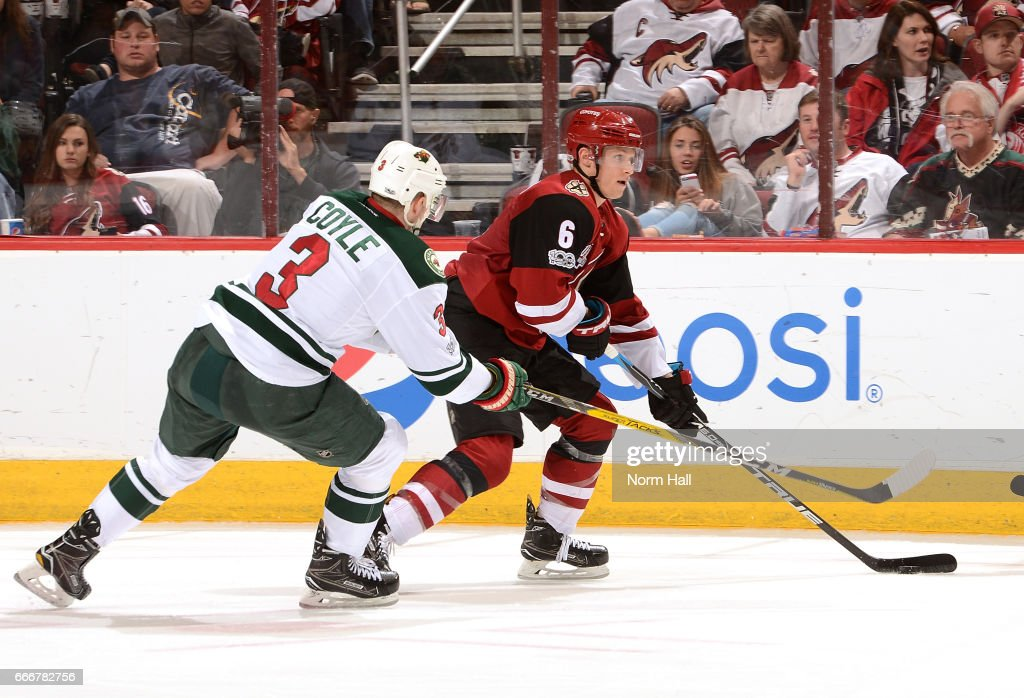 Jakob Chychrun #6 of the Arizona Coyotes skates with the puck while being defended by Charlie Coyle #3 of the Minnesota Wild at Gila River Arena on April 8, 2017 in Glendale, Arizona.