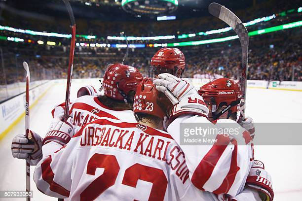 Jakob Forsbacka Karlsson of the Boston University Terriers and Jordan Greenway celebrate with Charlie McAvoy of the Boston University Terriers after...