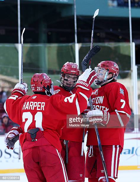 Jakob Forsbacka Karlsson of the Boston University Terriers celebrates with Patrick Harper and Charlie McAvoy after scoring against the Massachusetts...