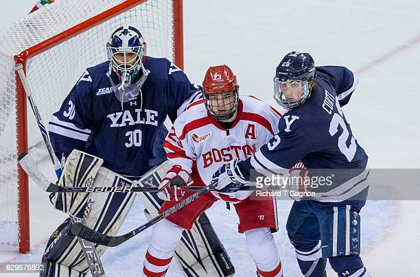 Jakob Forsbacka Karlsson of the Boston University Terriers is sandwiched between Patrick Spano of the Yale Bulldogs and his teammate Charlie Curti...