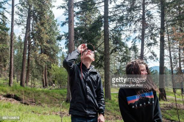Jakob Namson and Sarah Morris with their class from Lake City High School measure a tree at Farragut State Park in Idaho to learn about the effects...