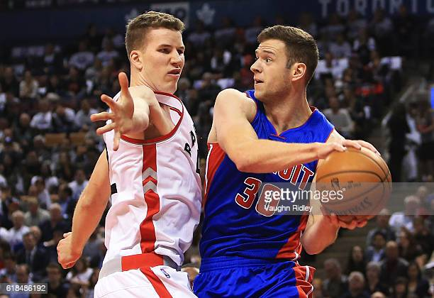 Jakob Poeltl of the Toronto Raptors defends against Jon Leuer of the Detroit Pistons looks to pass the ball during the first half of an NBA game...
