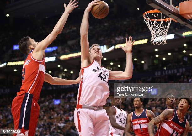 Jakob Poeltl of the Toronto Raptors pulls down a rebound against Tomas Satoransky of the Washington Wizards during NBA game action at Air Canada...