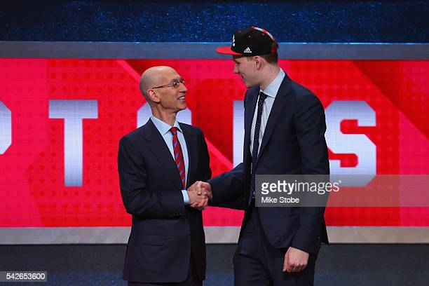 Jakob Poeltl shakes hands with with Commissioner Adam Silver after being drafted ninth overall by the Toronto Raptors in the first round of the 2016...
