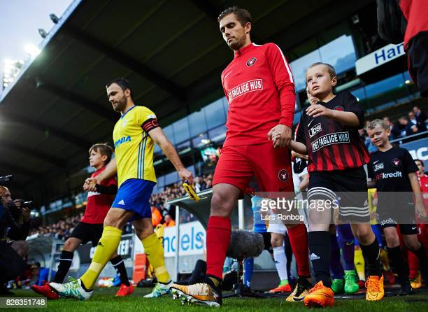 Jakob Poulsen of FC Midtjylland and Krzysztof Sobieraj of Arka Gdynia leading their teams on to the pitch prior to the UEFA Europa League...