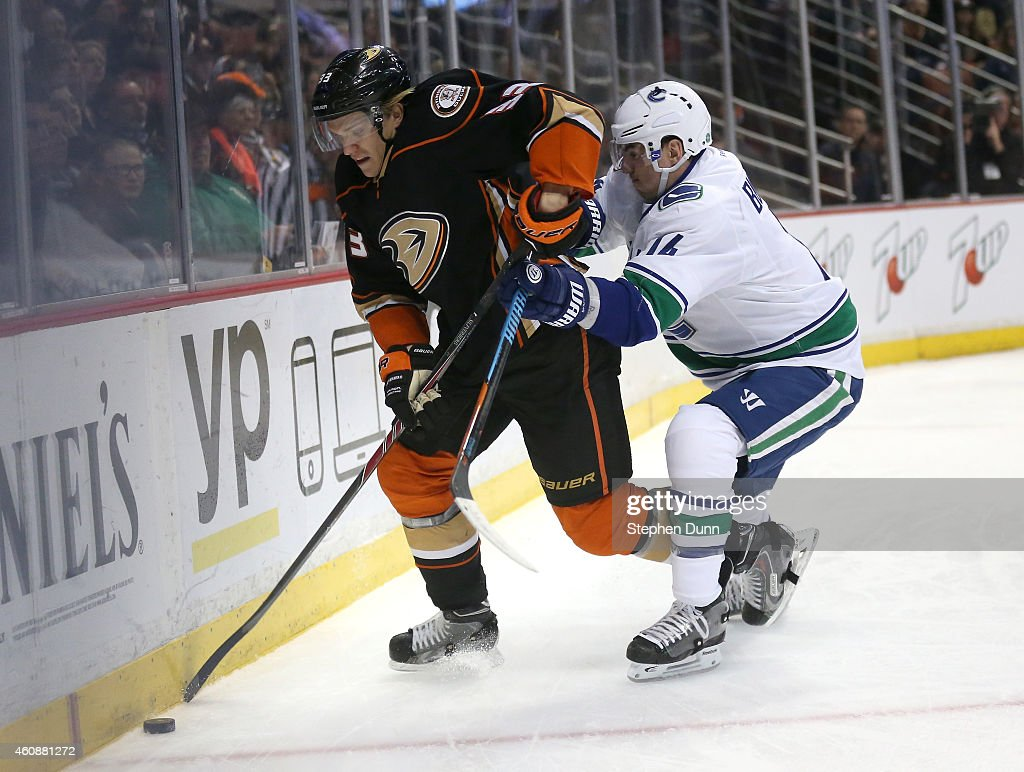 Jakob Silferberg #33 of the Anaheim Ducks fights for the puck with Alexandre Burrows #14 of the Vancouver Canucks at Honda Center on December 28, 2014 in Anaheim, California. The Ducks won 2-1 in overtime.