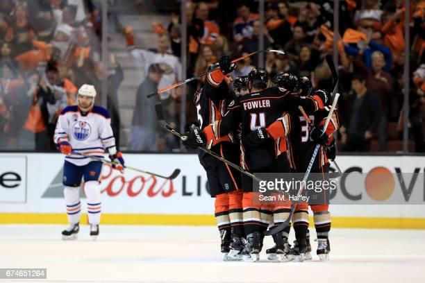 Jakob Silfverberg is congratulated by Cam Fowler and Ryan Getzlaf of the Anaheim Ducks after scoring a goal as Andrej Sekera of the Edmonton Oilers...