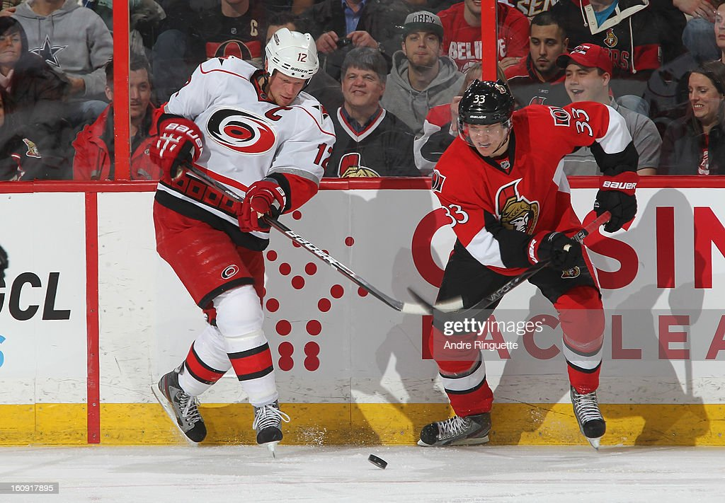 Jakob Silfverberg #33 of the Ottawa Senators battles for puck possession along the boards with <a gi-track='captionPersonalityLinkClicked' href=/galleries/search?phrase=Eric+Staal&family=editorial&specificpeople=202199 ng-click='$event.stopPropagation()'>Eric Staal</a> #12 of the Carolina Hurricanes on February 7, 2013 at Scotiabank Place in Ottawa, Ontario, Canada.