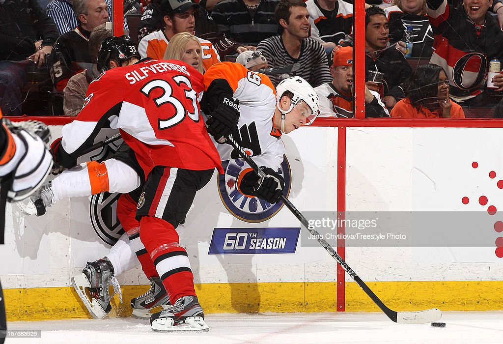 <a gi-track='captionPersonalityLinkClicked' href=/galleries/search?phrase=Jakob+Silfverberg&family=editorial&specificpeople=5894639 ng-click='$event.stopPropagation()'>Jakob Silfverberg</a> #33 of the Ottawa Senators checks <a gi-track='captionPersonalityLinkClicked' href=/galleries/search?phrase=Erik+Gustafsson+-+Ice+Hockey+Player+-+Born+1988&family=editorial&specificpeople=10836949 ng-click='$event.stopPropagation()'>Erik Gustafsson</a> #29 of the Philadelphia Flyers along the boards, during an NHL game, at Scotiabank Place, on April 27, 2013 in Ottawa, Ontario, Canada.