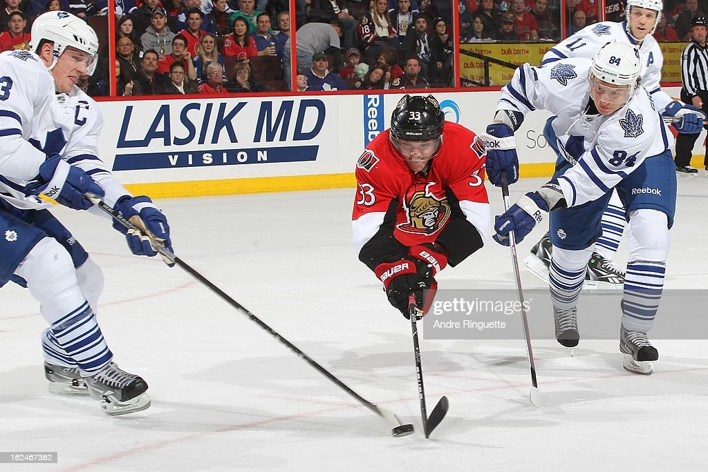 Jakob Silfverberg #33 of the Ottawa Senators goes airborne as he tries to control the puck against Dion Phaneuf #3 and Mikhail Grabovski #84 of the Toronto Maple Leafs on February 23, 2013 at Scotiabank Place in Ottawa, Ontario, Canada.