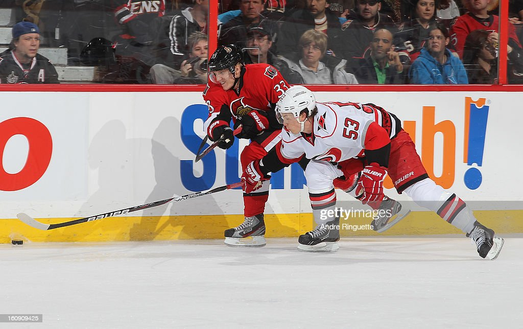 Jakob Silfverberg #33 of the Ottawa Senators passes the puck against pressure from Jeff Skinner #53 of the Carolina Hurricanes on February 7, 2013 at Scotiabank Place in Ottawa, Ontario, Canada.