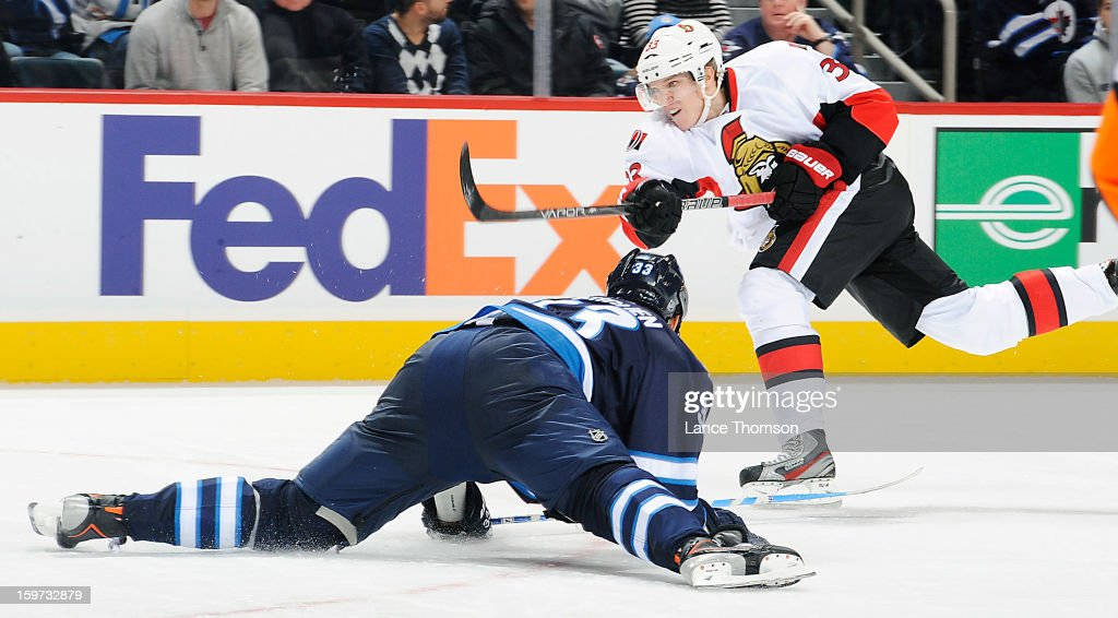 Jakob Silfverberg #33 of the Ottawa Senators shoots the puck over a sliding <a gi-track='captionPersonalityLinkClicked' href=/galleries/search?phrase=Dustin+Byfuglien&family=editorial&specificpeople=672505 ng-click='$event.stopPropagation()'>Dustin Byfuglien</a> #33 of the Winnipeg Jets during third period action at the MTS Centre on January 19, 2013 in Winnipeg, Manitoba, Canada.