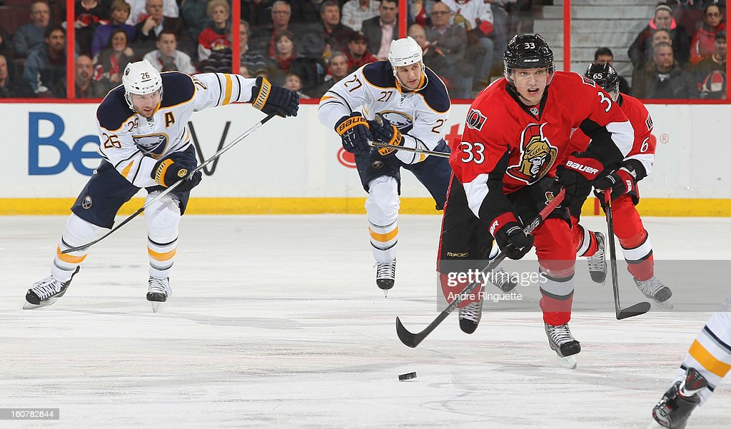 Jakob Silfverberg #33 of the Ottawa Senators skates up ice with the puck against Thomas Vanek #26 and Adam Pardy #27 of the Buffalo Sabres on February 5, 2013 at Scotiabank Place in Ottawa, Ontario, Canada.