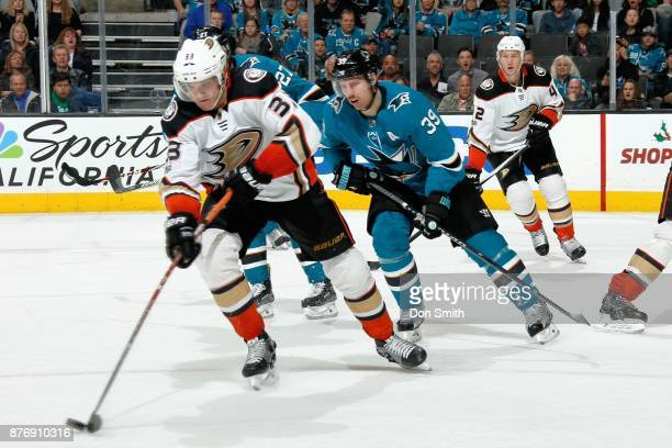 Jakob Silverberg of the Anaheim Ducks controls the puck ahead of Logan Couture of the San Jose Sharks at SAP Center on November 20 2017 in San Jose...