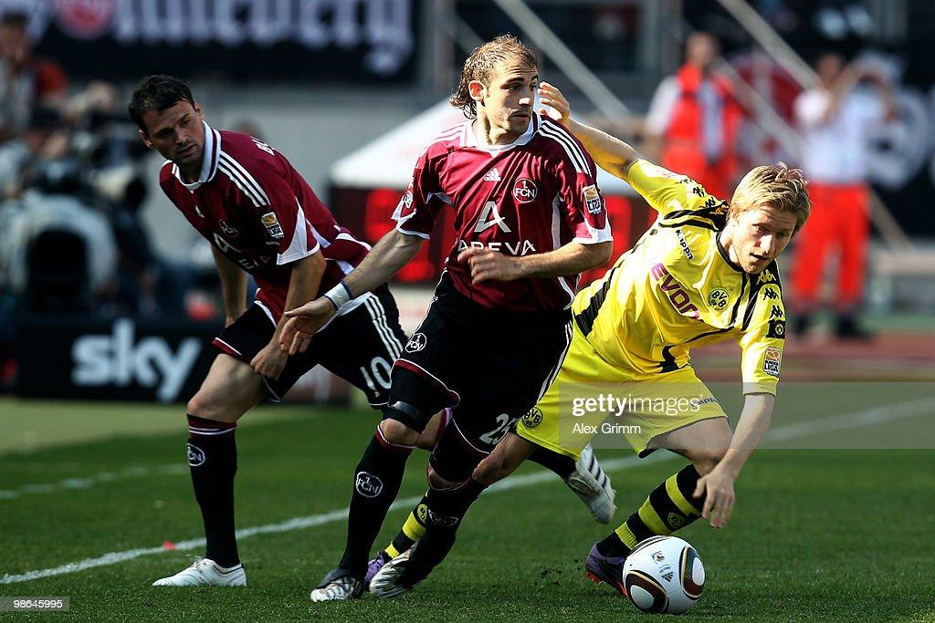 Jakub Blaszczykowski of Dortmund is challenged by Javier Pinola and Albert Bunjaku of Nuernberg during the Bundesliga match between 1 FC Nuernberg...