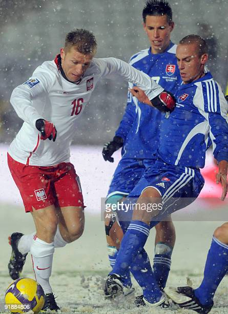 Jakub Blaszczykowski of Poland vies with Kamil Kapunek and Marek Kamsik of Slovakia during the 2010 World Cup Group 3 qualifier match between Poland...