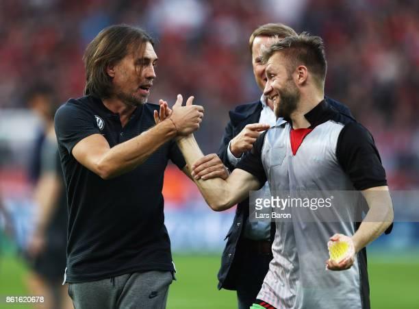 Jakub Blaszczykowski of VfL Wolfsburg is congratulated by Martin Schmidt head coach of VfL Wolfsburg after the Bundesliga match between Bayer 04...