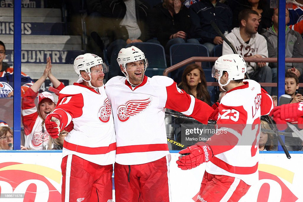 Jakub Kindl #4, Daniel Alfredsson and Brian Lashoff #23 of the Detroit Red Wings celebrate after a goal in a game against the Edmonton Oilers on November 2, 2013 at Rexall Place in Edmonton, Alberta, Canada.