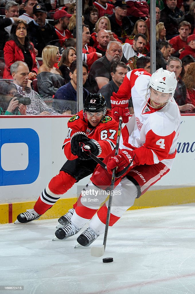 Jakub Kindl #4 of the Detroit Red Wings and Michael Frolik #67 of the Chicago Blackhawks skate with the puck around the boards in Game One of the Western Conference Semifinals during the 2013 Stanley Cup Playoffs at the United Center on May 15, 2013 in Chicago, Illinois.