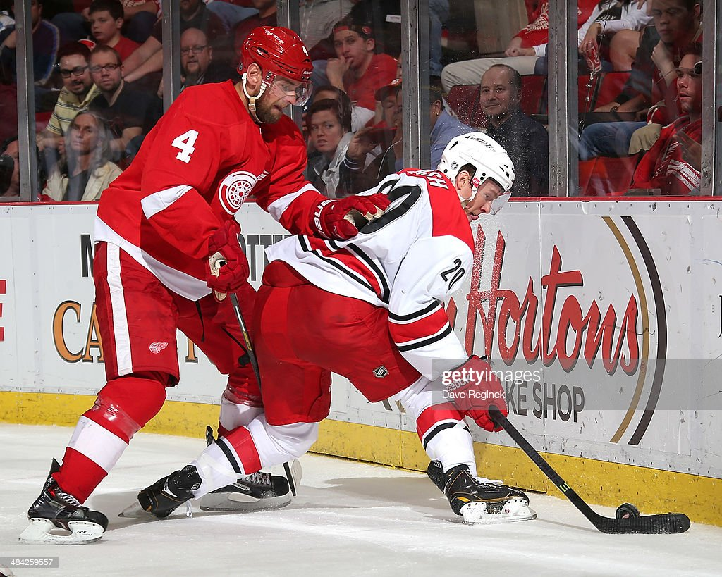 Jakub Kindl of the Detroit Red Wings and Riley Nash of the Carolina Hurricanes battle for the puck behind the net during an NHL game on April 11 2014...