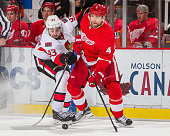 Jakub Kindl of the Detroit Red Wings controls the puck in front of Mika Zibanejad of the Ottawa Senators during an NHL game at Joe Louis Arena on...
