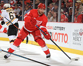 Jakub Kindl of the Detroit Red Wings fires the puck along the boards during a NHL game against the Boston Bruins on October 15 2014 at Joe Louis...
