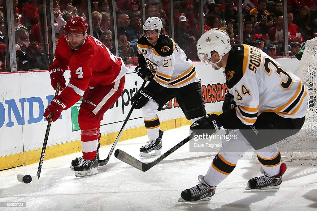 <a gi-track='captionPersonalityLinkClicked' href=/galleries/search?phrase=Jakub+Kindl&family=editorial&specificpeople=716743 ng-click='$event.stopPropagation()'>Jakub Kindl</a> #4 of the Detroit Red Wings handles the puck between <a gi-track='captionPersonalityLinkClicked' href=/galleries/search?phrase=Loui+Eriksson&family=editorial&specificpeople=2235241 ng-click='$event.stopPropagation()'>Loui Eriksson</a> #21 and Carl Soderberg #34 of the Boston Bruins during Game Four of the First Round of the 2014 Stanley Cup Playoffs on April 24, 2014 at Joe Louis Arena in Detroit, Michigan.