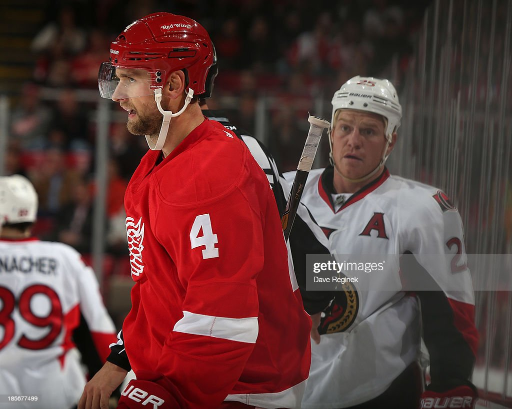 Jakub Kindl #4 of the Detroit Red Wings has words with Chris Neil #25 of the Ottawa Senators during an NHL game at Joe Louis Arena on October 23, 2013 in Detroit, Michigan.