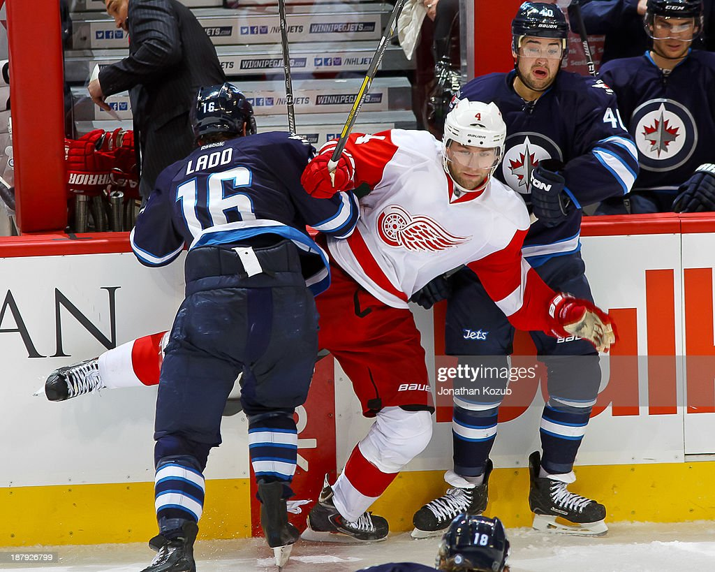 Jakub Kindl #4 of the Detroit Red Wings is sandwiched along the boards by Andrew Ladd #16 and Devin Setoguchi #40 of the Winnipeg Jets during third-period action at the MTS Centre on November 4, 2013 in Winnipeg, Manitoba, Canada. The Jets defeated the Wings 4-2.